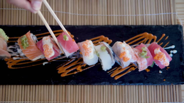 man eating sushi at japanese restaurant. - sushi video stock e b–roll