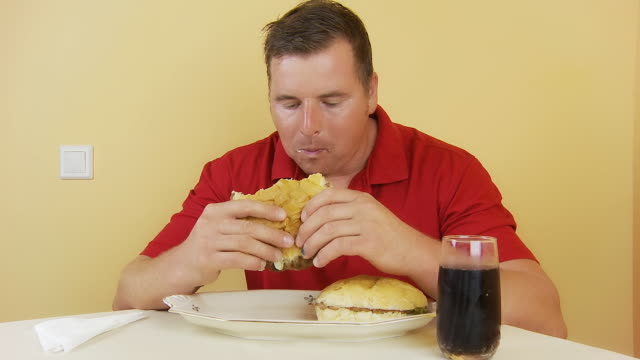 hd time lapse: man eating three hamburgers - over eating stock videos & royalty-free footage