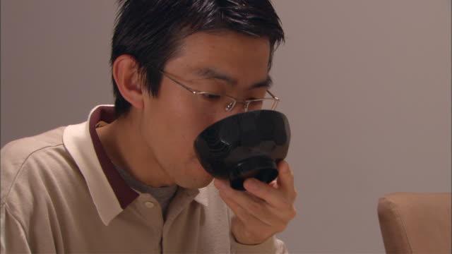 vídeos de stock e filmes b-roll de cu, man eating traditional japanese dinner - pauzinhos