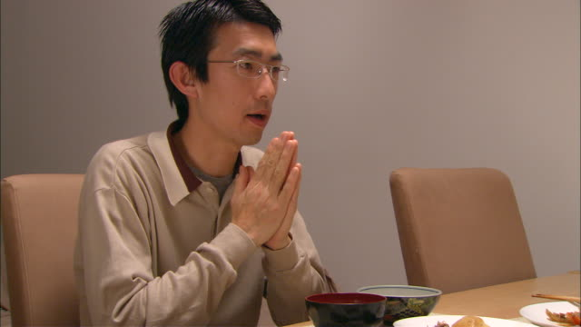 vídeos y material grabado en eventos de stock de cu, man eating traditional japanese dinner - manos juntas