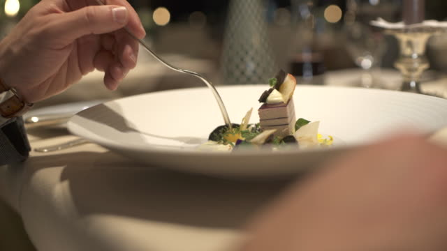 vídeos de stock e filmes b-roll de a man eats a salad when dining in a fancy luxury restaurant. - hotel
