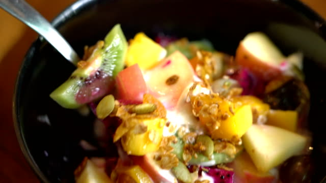 man eats bowl of healthy granola with fruits - kiwi fruit stock videos and b-roll footage