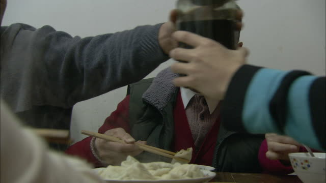 A man eats dumplings with chopsticks in Beijing.