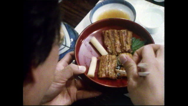 vidéos et rushes de man eats grilled eel with chopsticks in restaurant; 1989 - regarder vers le bas