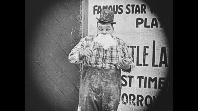 1919 man (fatty arbuckle) eats paste from a large brush after following the lead of a young boy who eats paste from his own face - glue stock videos & royalty-free footage