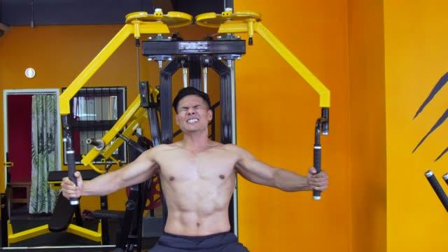 man effort to build muscle in fitness - attrezzatura per esercizio fisico video stock e b–roll