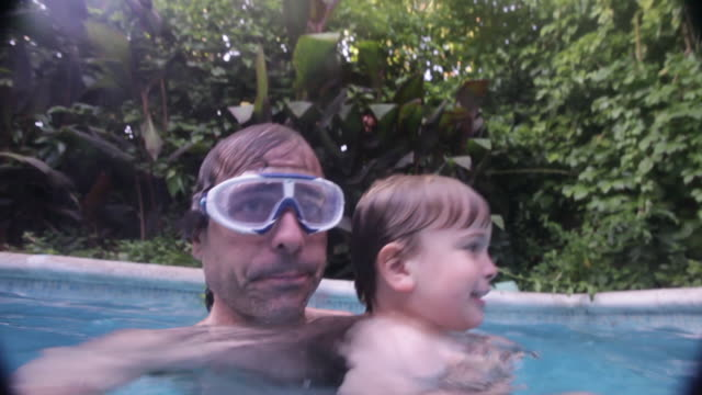 stockvideo's en b-roll-footage met man embraces little child (3 years)  while swimming in a swimming pool. summertime.madrid, spain. - buitenbad
