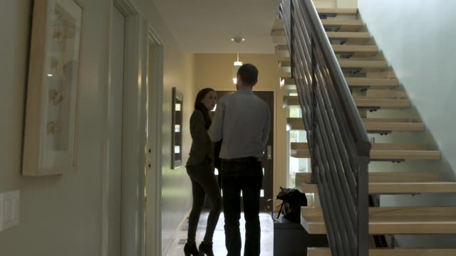 man embracing woman leaving home by front door. - leaving stock videos & royalty-free footage