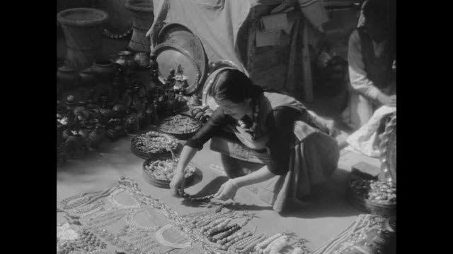 vídeos de stock e filmes b-roll de a man embroiders a rug hands carve a jade bracelet women display jewelry market sellers wait for customers and goods are weighed on the scale as a... - jade gema