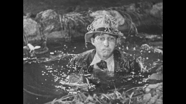 stockvideo's en b-roll-footage met 1932 man (bing crosby) emerges from a pond - bing crosby