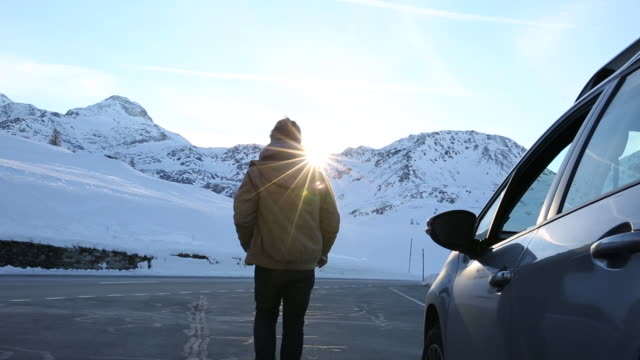Man emerges from vehicle, takes pic over mountains