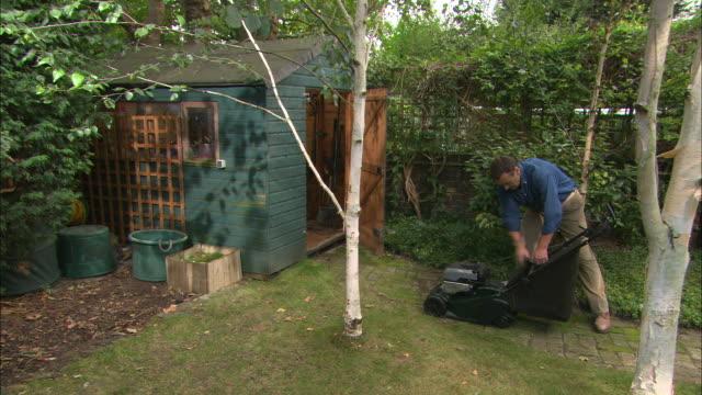 ws man empties grass cuttings onto compost heap next to ga - endast en medelålders man bildbanksvideor och videomaterial från bakom kulisserna
