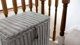Man emptying laundry bin into washing basket and walking downstairs