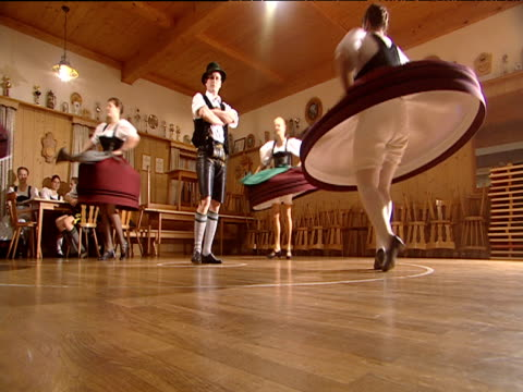 man encircled as female german folk dancers spin round in a circle performing schuplatter dresses flair into bell shapes revealing bloomers bavaria - bloomers stock videos & royalty-free footage