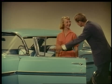 1957 man encourages woman to get into blue Chevrolet Impala in showroom