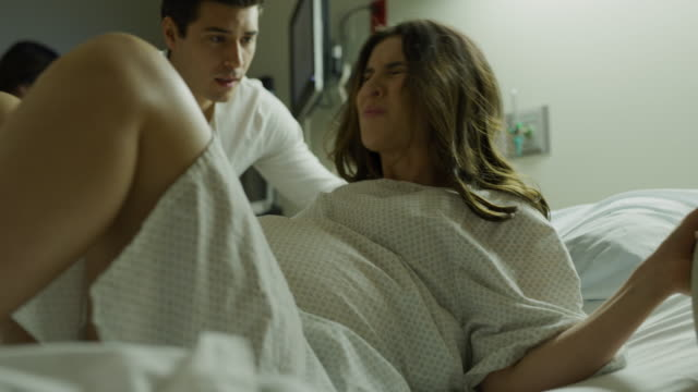 man encouraging pregnant wife laying in hospital bed having contractions / salt lake city, utah, united states - effort stock videos & royalty-free footage