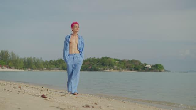 man enjoying a walk on the beach - pink hair stock videos & royalty-free footage