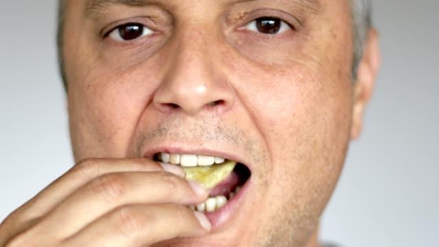 man enjoying eating potato chips - close up - salty snack stock videos & royalty-free footage