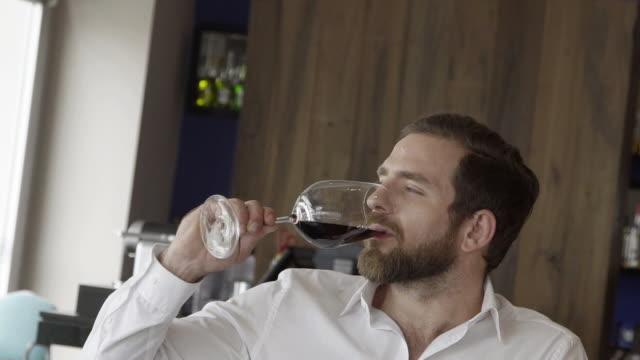 vídeos de stock, filmes e b-roll de man enjoying glass of red wine - copo de cerveja