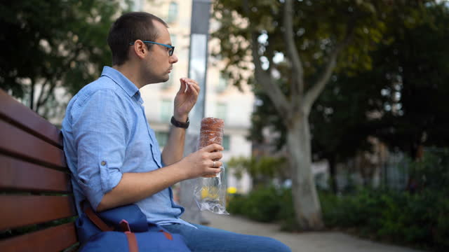man enjoying hungarian chimney cake - traditionally hungarian stock videos & royalty-free footage