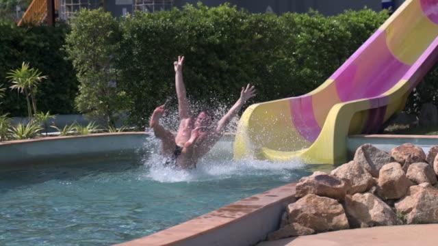 vídeos de stock, filmes e b-roll de homem apreciar em slides no parque aquático - tobogã d'água