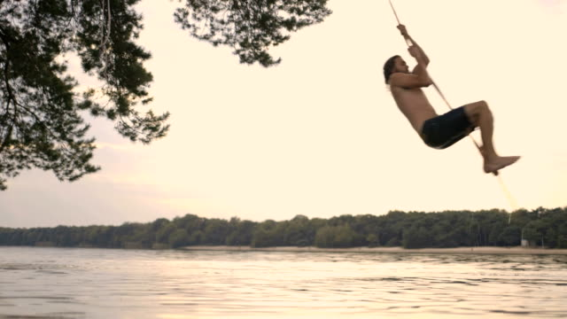 man enjoying rope swing over river. - swinging stock videos and b-roll footage