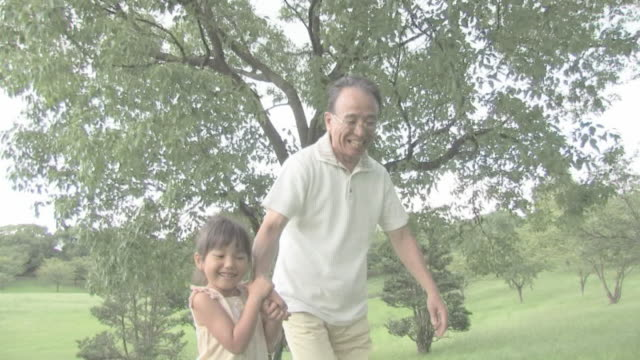 man enjoying walking with girl in park - grandchild stock videos & royalty-free footage