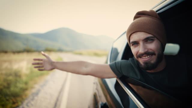 vídeos de stock e filmes b-roll de man enjoying wind through window of the car - interior de carro