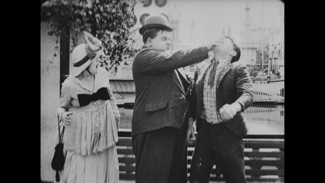 1917 man (fatty arbuckle) enjoys ice-cream with woman (alice mann) at amusement park until another man gets jealous and a fight ensues - spitting stock videos & royalty-free footage