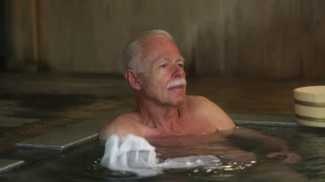 man enjoys japanese style bath - thermalquelle stock-videos und b-roll-filmmaterial