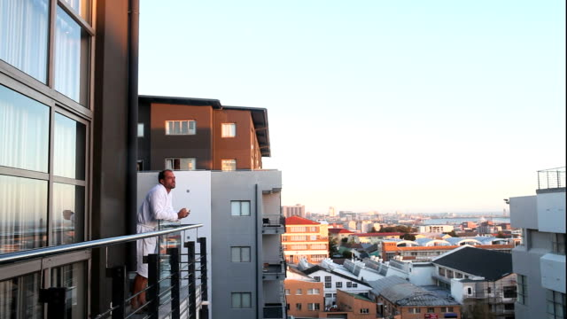 man enjoys morning coffee & sun - balcony stock videos and b-roll footage