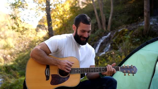 男を楽しむキャンプでギターを弾く - アコースティックギター点の映像素材/bロール