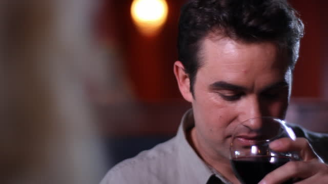 A man enjoys the aroma from his wine glass.