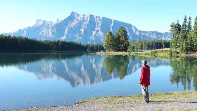 mann genießt aussicht in kanadischen rockies mount rundle am two jack lake - provinz alberta stock-videos und b-roll-filmmaterial