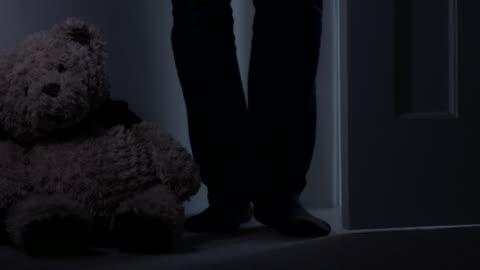 man går in i ett rum med mjuk leksak mot väggen. låg vinkelvy. - motljus bildbanksvideor och videomaterial från bakom kulisserna