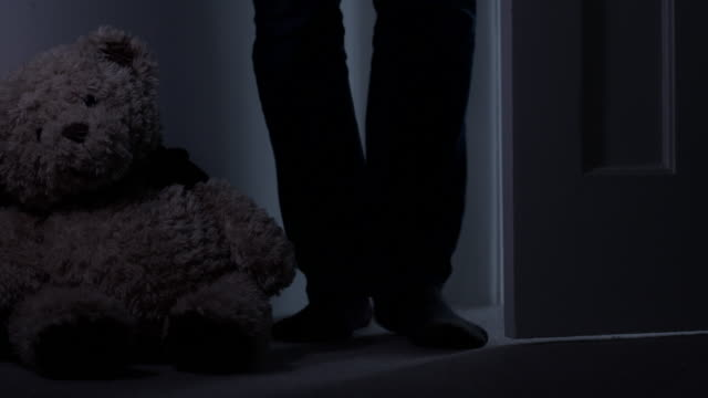 man entering a room with soft toy against wall. low angle view. - limb body part stock videos & royalty-free footage