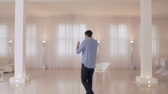 vídeos y material grabado en eventos de stock de ws of man entering frame , talking on mobile phone in apartment - toma ancha