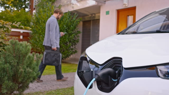 slo mo man entering his house while car is charging - nachhaltigkeit stock-videos und b-roll-filmmaterial