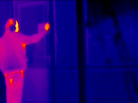 man entering house, thermography. the warm inside of the house is much brighter than the cold exterior.. - thermal imaging stock videos & royalty-free footage