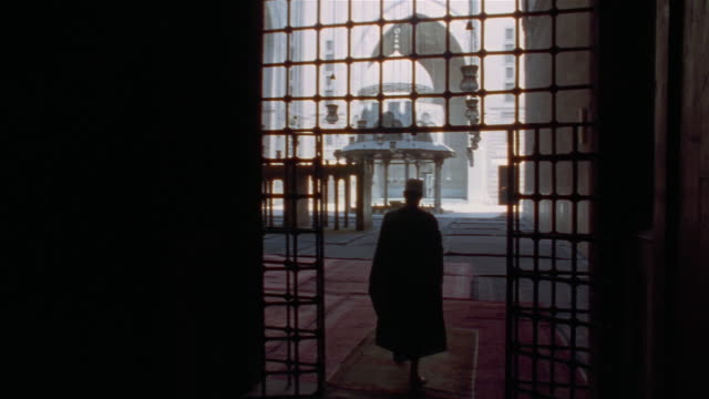 ms, pan, man entering sultan hassan mosque courtyard, rear view, cairo, egypt - madressa stock videos and b-roll footage