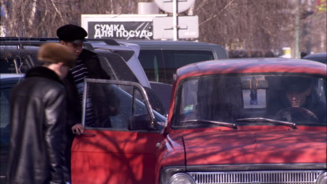 a man enters a car on a congested street. available in hd. - kazakhstan stock videos & royalty-free footage