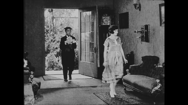 1922 Man (Buster Keaton) enters a house and a woman (Madge Kennedy) throws him a bouquet of daisies / once inside, they kiss and he presents the bouquet to her