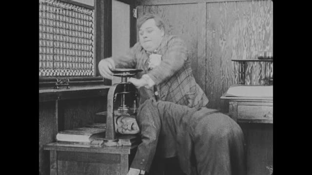 1918 Man (Fatty Arbuckle) enters bank, is hit by a vase that his supervisor throws at the other group of robbers, and tightens a vise around the head of one of the robbers