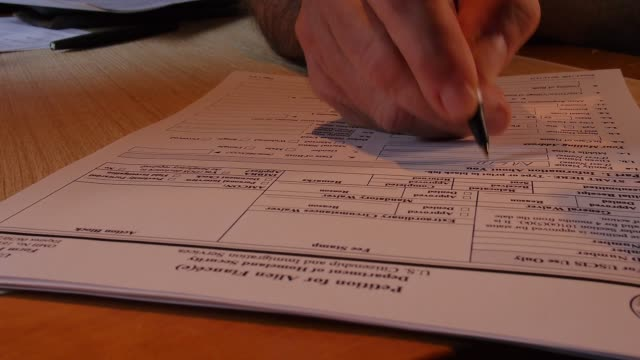 A man enters information on a mockup of a form used to petition the US government to allow a nonresident to enter the country as a fiancee of a...