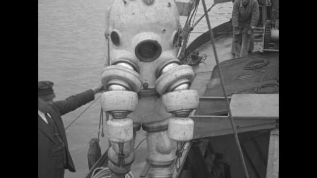 vídeos de stock, filmes e b-roll de man enters small hatch of apparatus / vs top of suit with articulated arms is lowered / vs man inside suit moves arms and legs while dangling over... - deep sea diving