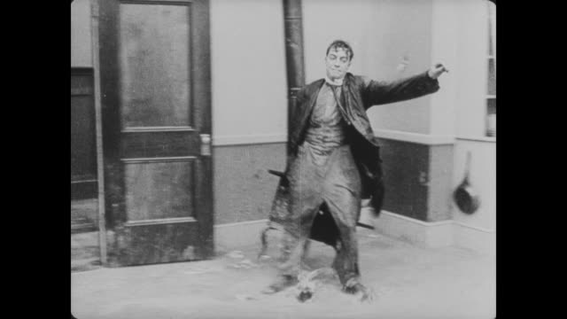 vidéos et rushes de 1920 man (buster keaton) enters the spinning house, is thrown around in circles, and falls back through the door and outside - trébucher