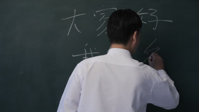 vidéos et rushes de ms man erasing chinese characters from blackboard / singapore - salle de classe
