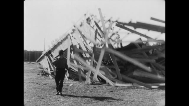 vidéos et rushes de 1928 a man (buster keaton) escapes from a house moments before it succumbs to storm winds - évasion