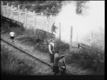 vidéos et rushes de man escaping thru barbed wire fence of berlin wall as guards watch / germany / newsreel - 1961