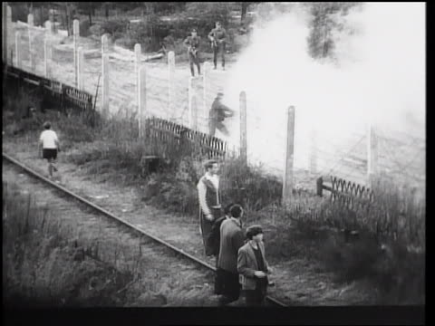 vídeos de stock, filmes e b-roll de b/w 1961 man escaping thru barbed wire fence of berlin wall as guards watch / germany / newsreel - fronteira internacional